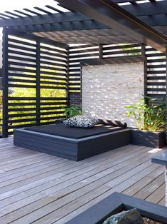 This built-in outdoor daybed with a stone wall and planters sits underneath a pergola that provides shade.