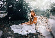 Девушка в белом платье сидит на траве в окружении бабочек