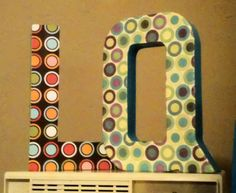 Cardboard letters covered in acrylic paint, scrap booking paper and mod podge.