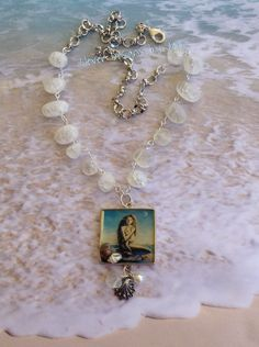 A Sweet Mermaid picture that is mounted into a mold along with a couple of shells,  resin was used to seal the picture ..  ..dangling from the bottom is a B'sue clam shell, pearl and a white stone .. white stones and B'sue silver chain finish this necklace off .. Jann Tague .. Clever Designs .. https://www.facebook.com/JewelsByJann