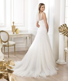 Pronovias 2014  Lacinne Tulle wedding dress with silver and mother-of-pearl gemstone embroidery. V-neck, semi-sheer draping on the shoulders, grosgrain belt with bow at the front and tulle skirt with godets.