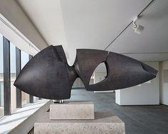 """Aclopotesis"", Escultura realizada en madera tintada en pátina negra. Montada sobre base de acero inoxidable y soportada por un eje central. · Proyecto original 137 x 35 x 25 cm"