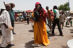 Fati Abubakar takes photos of daily life at a market in Maiduguri, Nigeria, a regional capital where Boko Haram started out, June 17, 2016.  (Jane Hahn/The New York Times)