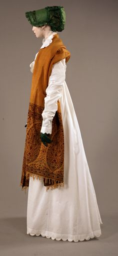 "From the exhibition ""Napoleon and the Empire of Fashion"". Lancaster - Barreto collection. Redingote: Cotton percale, Beige cotton thread embroidery, France, circa 1808. Shawl: Cashmere and silk. India, circa 1810. Hat: Green, taffetas, satin and silk cording, France 1808. Lunettes: Vermeil, green chagrin, France circa 1800. Gloves: Green kid, England, first quarter of the XIX century."