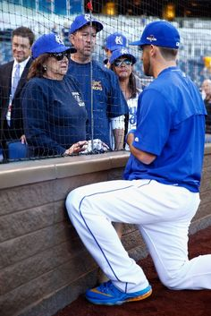 Drew Butera ,KC, speaks with family members of two KCFD firefighters who lost their lives battling a structure fire earlier in the week prior to game five , ALDS v HOU, October 14, 2015