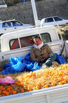 Bhutanese youth on a bed of oranges