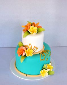 Tropical wedding cake in teal blue and white, 2 tier wedding cake, plumerias on each tier with a fondant finish.