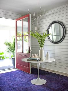 In this entryway, shiplap paneling adds classic character and a red door makes for a vibrant first impression. A simple and modern light fixture makes the space feel a bit more contemporary, while a purple area rug in a subtle print brings a much-needed pop of color. A round mirror and entry table add circular edges to the geometric lines of the shiplap./