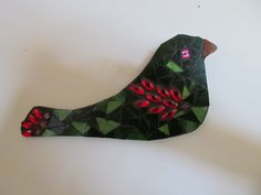 Green long tailed bird made with stained glass, has bright red wing and tail and completed with millifiori beads