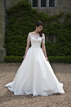 Sian - Demure elegance. This lovely wedding gown features a lace boatneck bodice with sheer sleeves that just clip the shoulders. The A-line organza skirt flows out from a tiny satin belt at the waist. Covered buttons add the finishing touch.