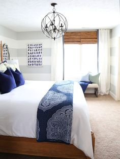 Blue and white guest bedroom with natural wood accents and striped walls. Love this before & after home tour!