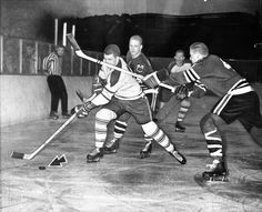 Blackhawk defensman Elmer 'Moose' Vasko, right, had a busy night on March 5, 1961 at the Chicago Stadium. Vasko shoves his stick under the nose of Toronto's Carl Brewer during Brewers attempt to advance the puck. Behind Brewer during first period action is the Hawks' Bobby Hull.