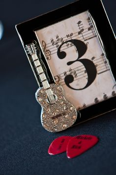 "Rock N Roll #Wedding table marker!     ""The theme of our wedding was ""Rock and Roll"" my friends and I found these frames at various Michaels craft stores and my sister in law placed the background paper and #'s in them.  We also had personalized guitar pics made with our names and date"""