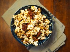 In this addictive popcorn recipe, rich brown butter and maple syrup are cooked into a quick caramel, which is then used to both candy the pecans and coat freshly popped popcorn. A generous pinch of salt makes all those sweet-savory flavors pop.