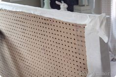 back of padded head board for bed.  The holes make it easy to tuft with buttons on the front.... cool idea!