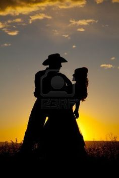 A cowboy is holding a woman in the sunset and dipping her