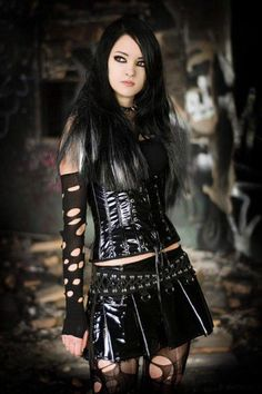 Goth woman in loose black latex corset and black latex skirt, with torn sleeves, stockings, and spiked collar