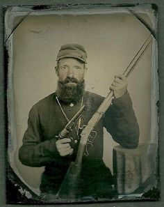 Ninth plate ambrotype of Confederate soldier with an 1851 Colt Navy pistol and Edwin Wesson rifle.