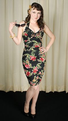 Leilani Hawaiian Hibiscus Dress:This sexy Hawaiian adjustable halter wiggle dress has a gorgeous pink hibiscus pattern on black cotton, an adjustable tie at the bustline, and figure-flattering shirring at the waist to make you look nipped in. It has a hidden back zipper and a back slit at the hem for easy movement. 100percent cotton, Machine washable and Made in the USA. Size... $112.00