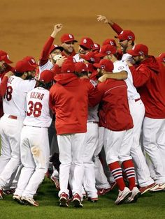 Cardinals players celebrate on the field after winning Game 6.