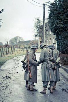 German soldiers on a road in probably france. I wonder what they are doing. Looking at a map?