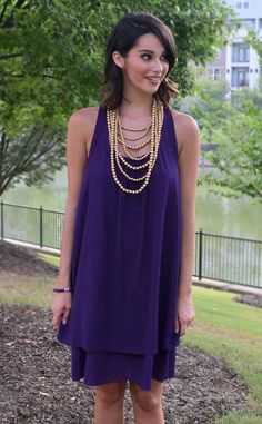 This fun purple shift dress is a stunning look for LSU Gameday or a night on the town. This stunning double layered tiered ruffle hem goes great with the flirty ruffled racer-back and on-trend flowy shift cut. Super chic and comfy, we know you'll turn heads in this versatile number!