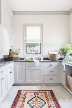 Alyssa Rosenheck - Austin Bean Design Studio - A vintage rug sits in the center of a gray u-shaped laundry room fitted with light gray cabinets accented with nickel cup pulls and a dark gray quartz countertop. Decor, Kitchen Decor, Bedroom Design, Home Decor, Room Inspiration, Light Gray Cabinets, Kitchen Rug, Large Laundry Rooms, Kitchen Design