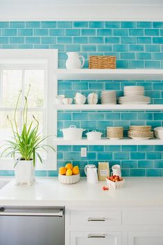 Meg Braff Designs - Stacked white floating shelves are mounted on ocean blue subway tiles beside a window fixed above a stainless steel dishwasher positioned under a white quartz countertop complementing white inset kitchen cabinets.