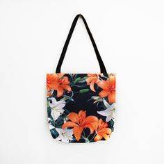 Tropical Lilies on Black Tote Bag. Floral print with bright orange and white lily flowers. Canvas bag, carry all bag. Apparel accessory. Pretty print. Available to buy on Society6, design by Tamsinlucie.