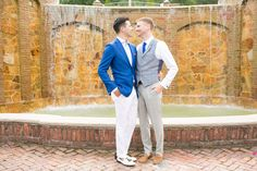 Mikkel Paige Photography photos of a summer, daytime gay wedding.  An image of the grooms in a vest and blue suit in front of a picturesque fountain at The Manor, in West Orange New Jersey.