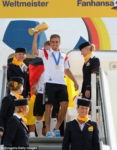 Captain Philipp Lahm holds up the World Cup as the victorius German national team returns ...