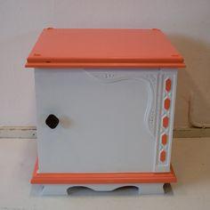 Kastje opgepimpt in de kleur oranje/wit. Leuk als nachtkastje of als bijzetter. Het kastje heeft nog het originele kastknopje. Een leuk detail zijn de ruitjes aan de zijkant van het kastje.