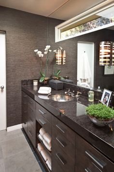 Although maybe a tad too dark overall, I like several elements of this design: the cabinet layout (including towel nook), the sconce, the transom window, the one-piece mirror and the wall treatment (or tile?)