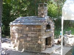Outdoor pizza oven/wood stove!  Love how it looks like a little house!