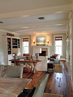 Realistic decorating. Love the fireplace, the hardwoods, and the charming sconce light.