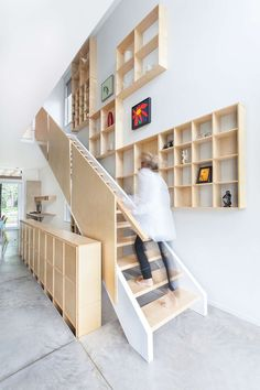 12 Inspiring Examples Of Staircases With Bookshelves | These plywood shelves that follow the stairs up are a great place to store books and display art or other decorative items.