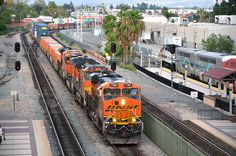 """BNSF ES44C4 7165 leads an intermodal train through Fullerton Junction, and into the Amtrak / Metrolink station, as it heads to Los Angeles on June 12th, 2015. In moments, this train will meet Amtrak #4, the """"Southwest Chief,"""" on its way to Chicago. Meanwhile, over on Track 4 is the Metrolink Fullerton to Laguna Niguel shuttle. Photo by RockAndRail."""