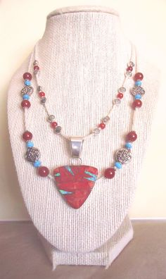 "Rhapsody in red!  This elegant, multi-strand statement necklace was hand-crafted from ivory colored glass accented by natural red agate (inner strand), matching natural carnelian (outer strand), natural blue turquoise and silver-plated knotwork fittings, then crowned by a one-of-a-kind Zuni inlay pendant (measures just under 1 1/2"" x 2 1/4"" - including bail) made from red spiny oyster shell and blue / green fire opal, set in sterling silver by a Native American silversmith.  Enjoy :)"
