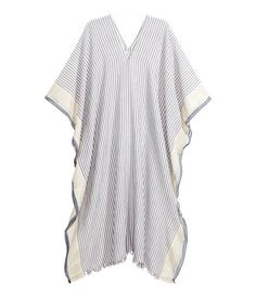 Natural white/blue stripe. Poncho in airy woven fabric with glittery threads. Button at sides and fringe at hem. Size 39 1/4 x 86 1/2 in.