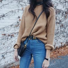 Elongate your legs by slightly tucking in a sweater into high waisted jeans—it's a simple fall look that makes a statement.
