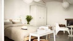 """Quarto """"Bed & Breakfast"""" decorado com uma cama de pinho maciço e um roupeiro e banco brancos"""