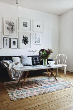 parede com quadros em preto e branco na decoração com mesa de centro com pés palito, sofá de couro e tapete étnico