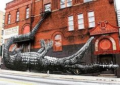 """""""Upside Down Alligator"""" by #Roa in downtown Atlanta. This piece was part of the city's Living Walls project which brought street artists in to gentrify neighborhoods from 2010-2014. Love the incredible detail and the stunning incorporation of the fire escape that forms the tail, a must see when you are in town.  #Atlanta #streetart #contemporaryart #streetartistry #livingwalls #urbanart #alligator #alligatorart"""
