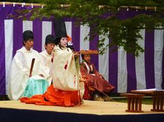 A shirabyoshi dancer along with men and a boy, all dressed in kariginu