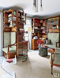At the upstate New York farmhouse of antiques maven Bernd Goeckler and designer Carl D'Aquino, the library boasts early-20th-century carved-oak cabinetry by Paul Jouve and Eugène Grasset. The seating is clad in a Maharam fabric, the 1950s brass-and-glass stepladder is attributed to FontanaArte, the low table at right is by Philip and Kelvin LaVerne, and the sisal is by Stark.