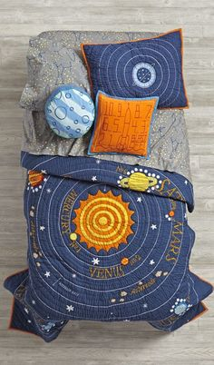 """Let the countdown to bedtime begin. Our out-of-this-world Solar System quilt features our eight official planets orbiting the sun. Feeling sorry for Pluto? We've paid homage to the cute dwarf planet in a top-of-the-bed, reversible throw pillow. Complete the universe with our Stars and Orion's Sheet Sets. Don't forget a """"Blast-Off"""" throw pillow."""