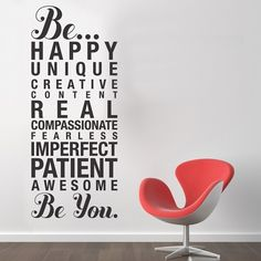 Be yourself wall decal in matte black on a white wall featuring a large manifesto of quotes in a rectangular shape. This decal reminds you to be happy, real, patient, etc. and is seen behind a red modern chair in this scene.