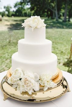 Brides: Simple Three-Tiered White Cake with Flowers. A three-tiered white wedding cake with piped details and fresh flowers created by Confectionery Designs.