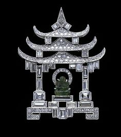 Platinum diamond and emerald brooch of a shrine. c.1927.  The architecture, which is entirely carried out in diamonds of various cuts - circular, emerald, baton - culminating in the trapezoid shaped stones at the apex of the roof, encloses a carved emerald Buddhist divinity raised up on steps.