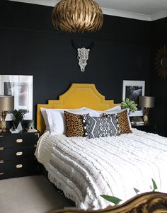 boho glam bedroom with yellow headboard and black walls